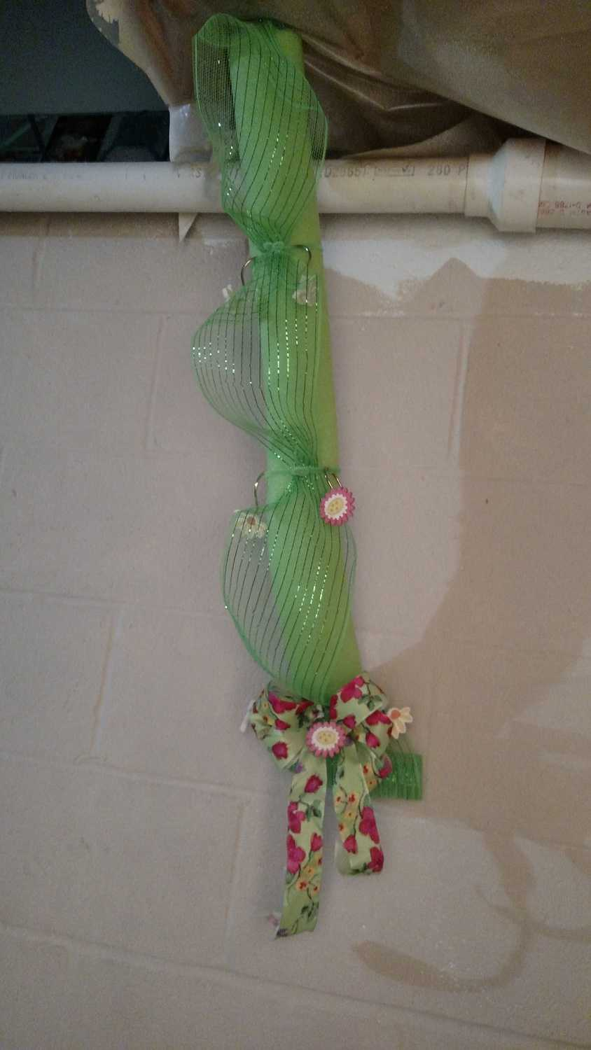 pipe disguised with pool noodle, deco mesh, flower shower curtain hooks, and a bow