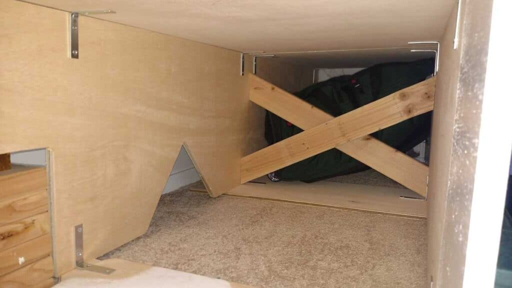 underneath storage bed, with access holes to electrical outlets