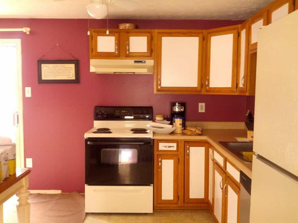 kitchen wall facing stove, with cabinets and red wall