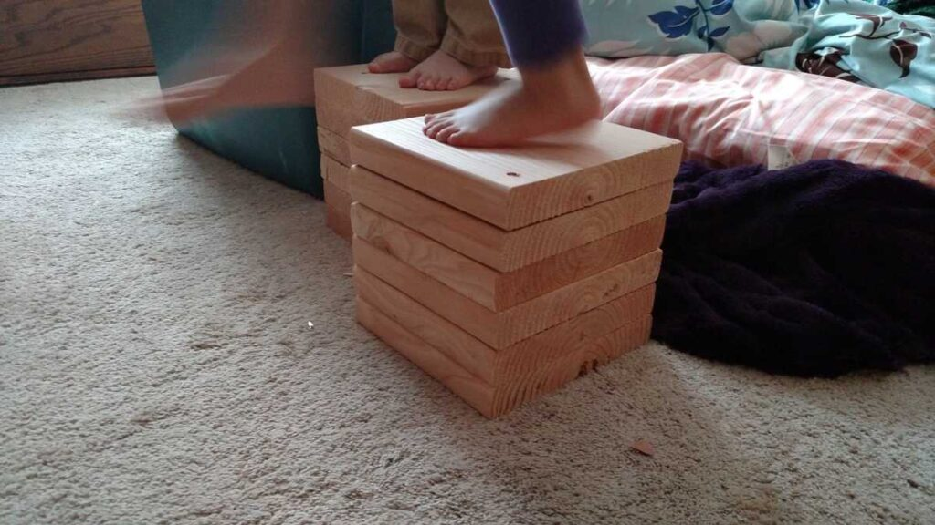 stack of wooden block with children's feet standing on them