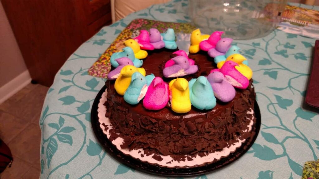 chocolate cake with various colors of marshmallow chicken peeps on it