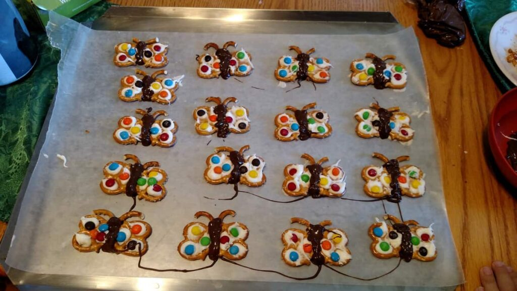 Butterfly chocolate covered pretzels in rows drying on wax paper