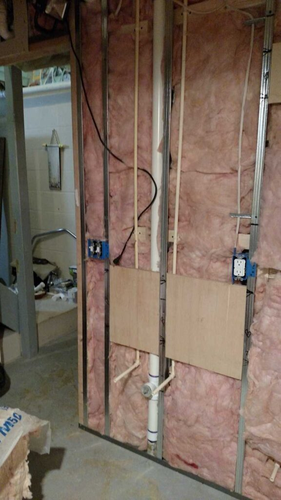 bathroom wall showing insulation, electrical wiring, and water pipes exposed