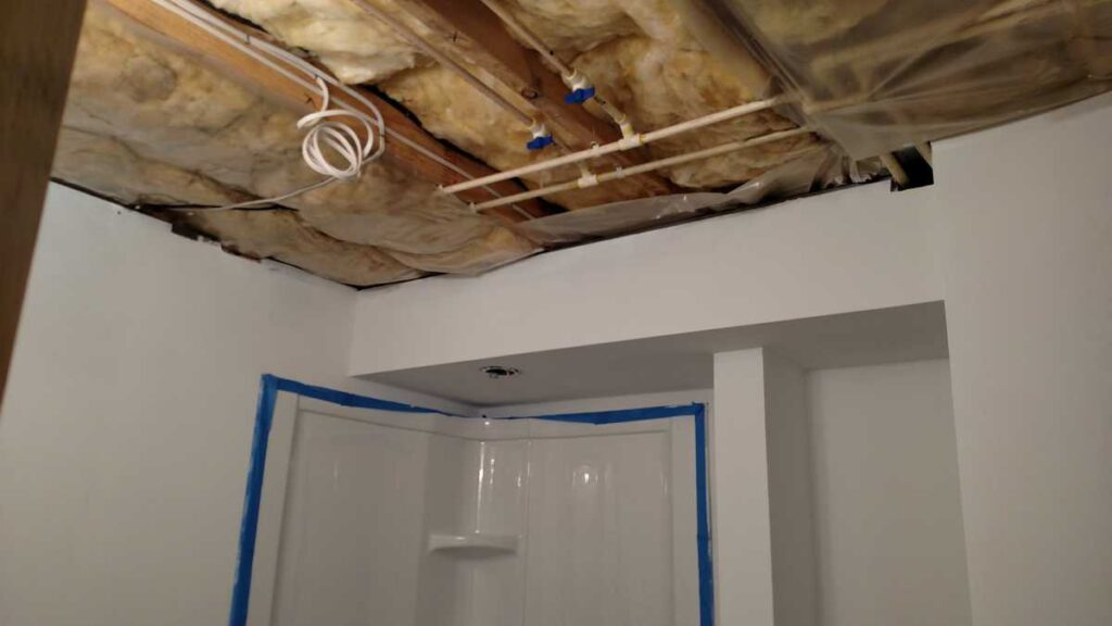 exposed ceiling showing water pipes and insulation