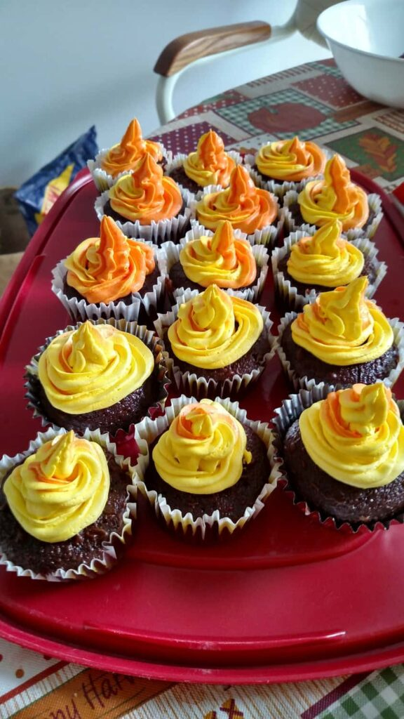 yellow and orange swirled frosting on cupcakes