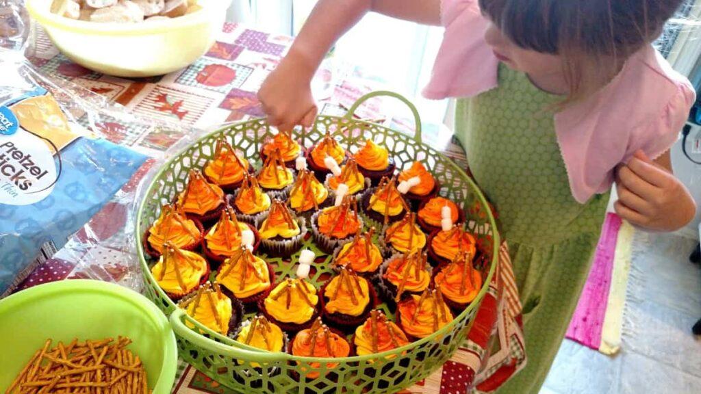 little girl putting marshmallow toothpicks onto cupcakes