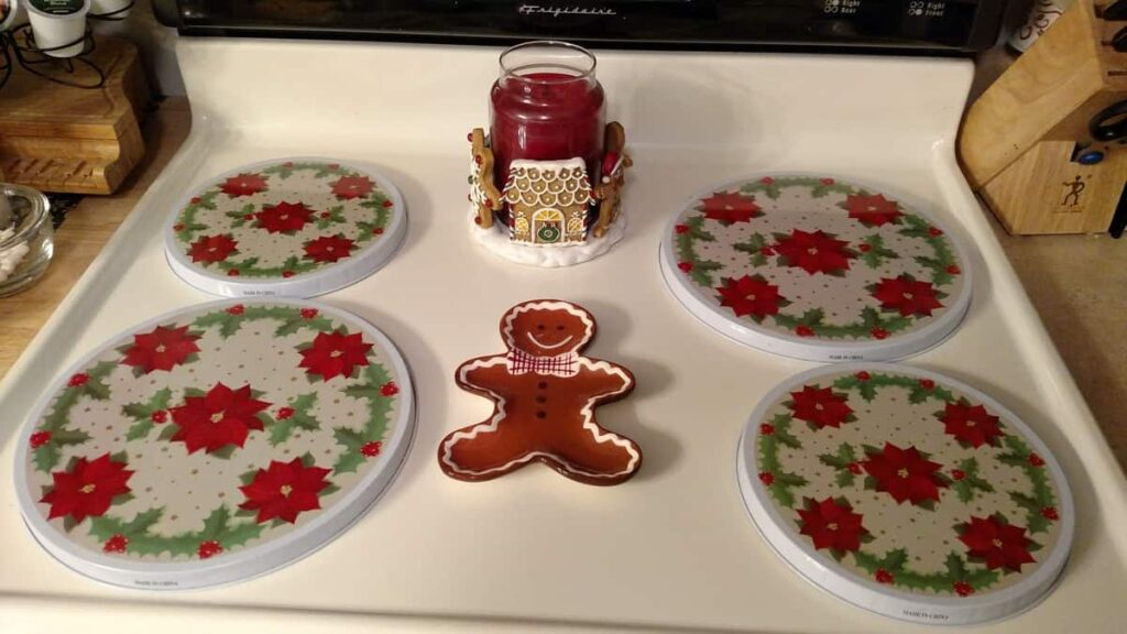 Christmas stovetop with poinsettia burner covers with gingerbread spoonrest and gingerbread candle holder