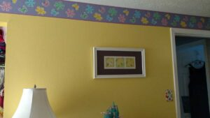 girls room painted yellow with flower wallpaper border near ceiling