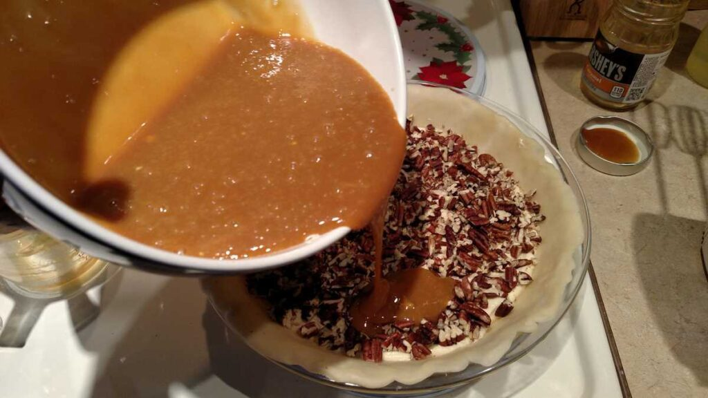 bowl pouring caramel sauce over nuts in pie
