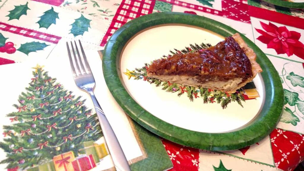 Christmas tree napkin and paper plate with pie lined up on the Christmas tree