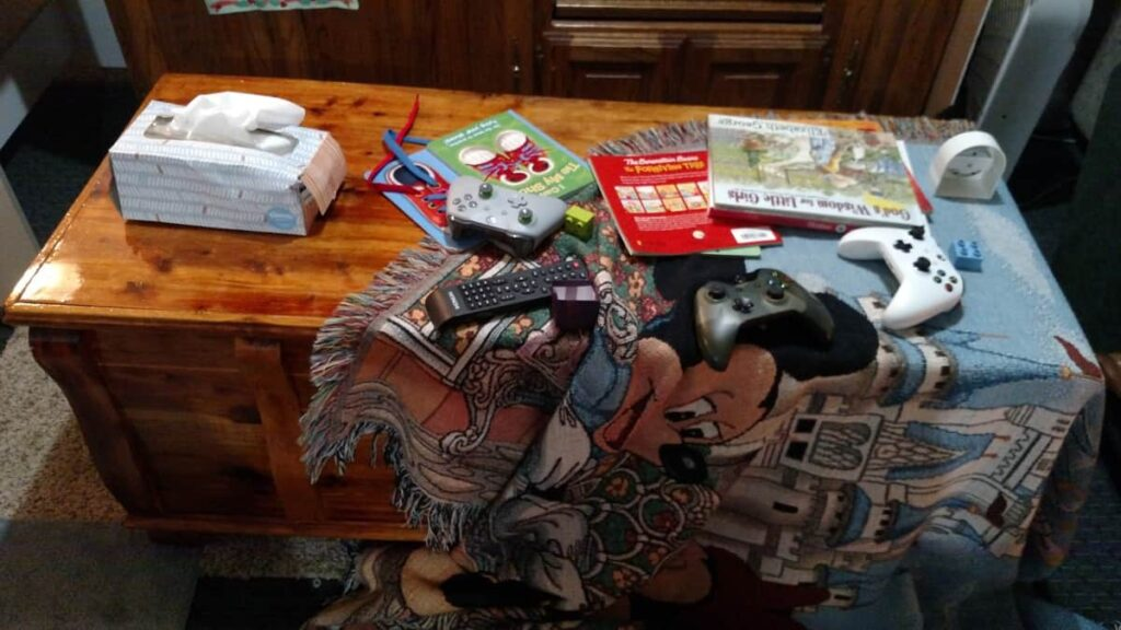 cedar chest with blanket, books, game controllers, tissue box, all disorganized and messy