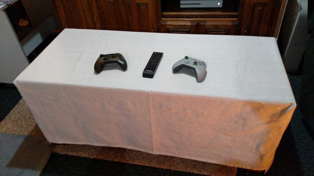 white slipcover with two game controllers and a remote sitting on it