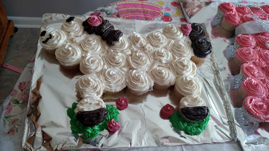 white frosted cupcakes in the shape of a horse, with green grass detail and some pink flowers