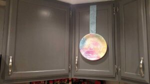 kitchen cabinet with paper plate hanging from ribbon