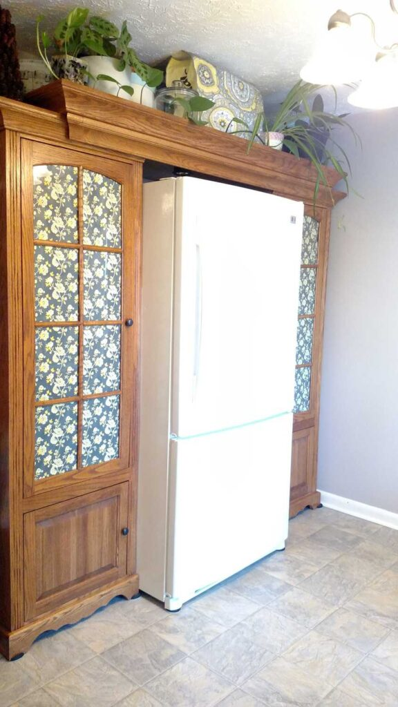 side view of the fridge with cabinets as pantries on each side