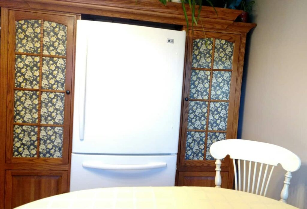 front view of the fridge with entertainment center pantries on each side