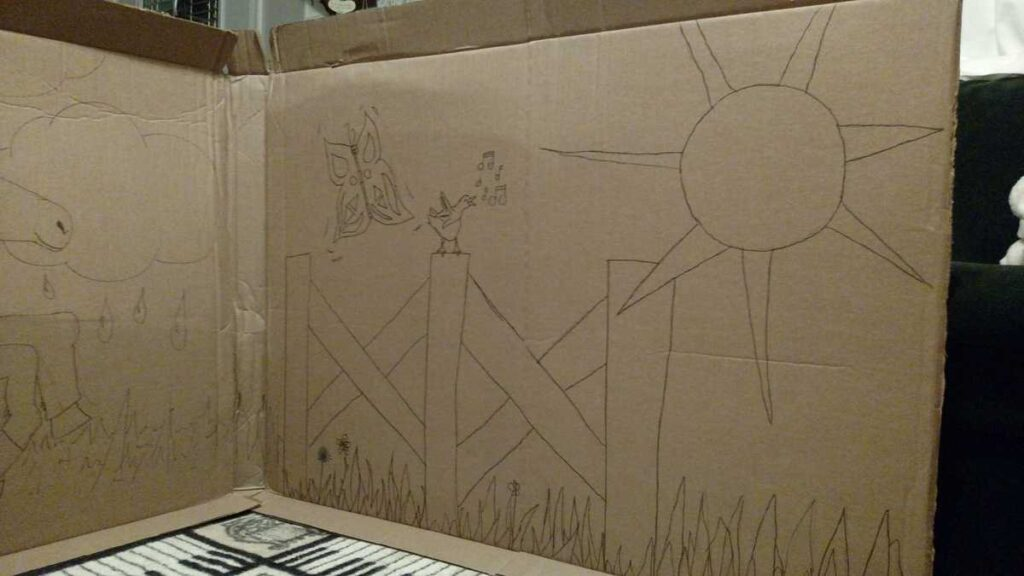 the fence side of an outdoor scene including the sun and butterflies, drawn on a large piece of cardboard