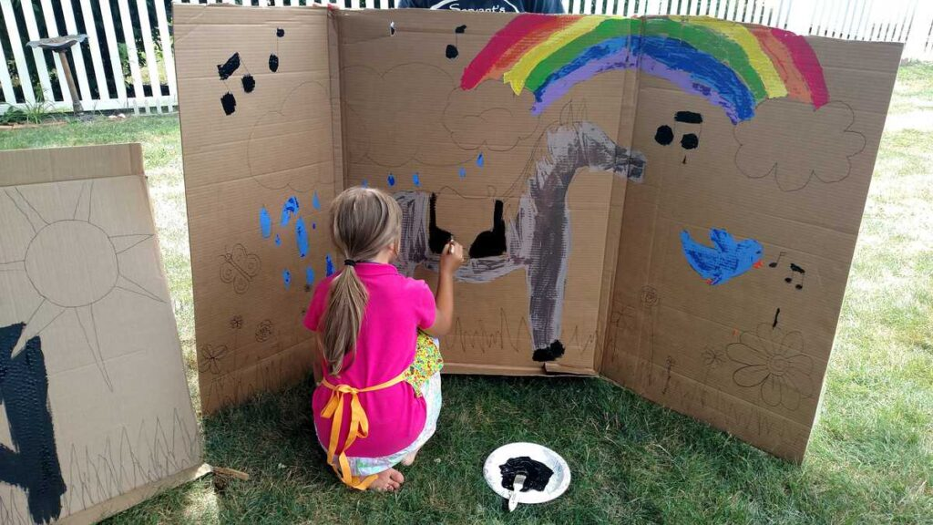 child painting large horse scene on a cardboard outdoors