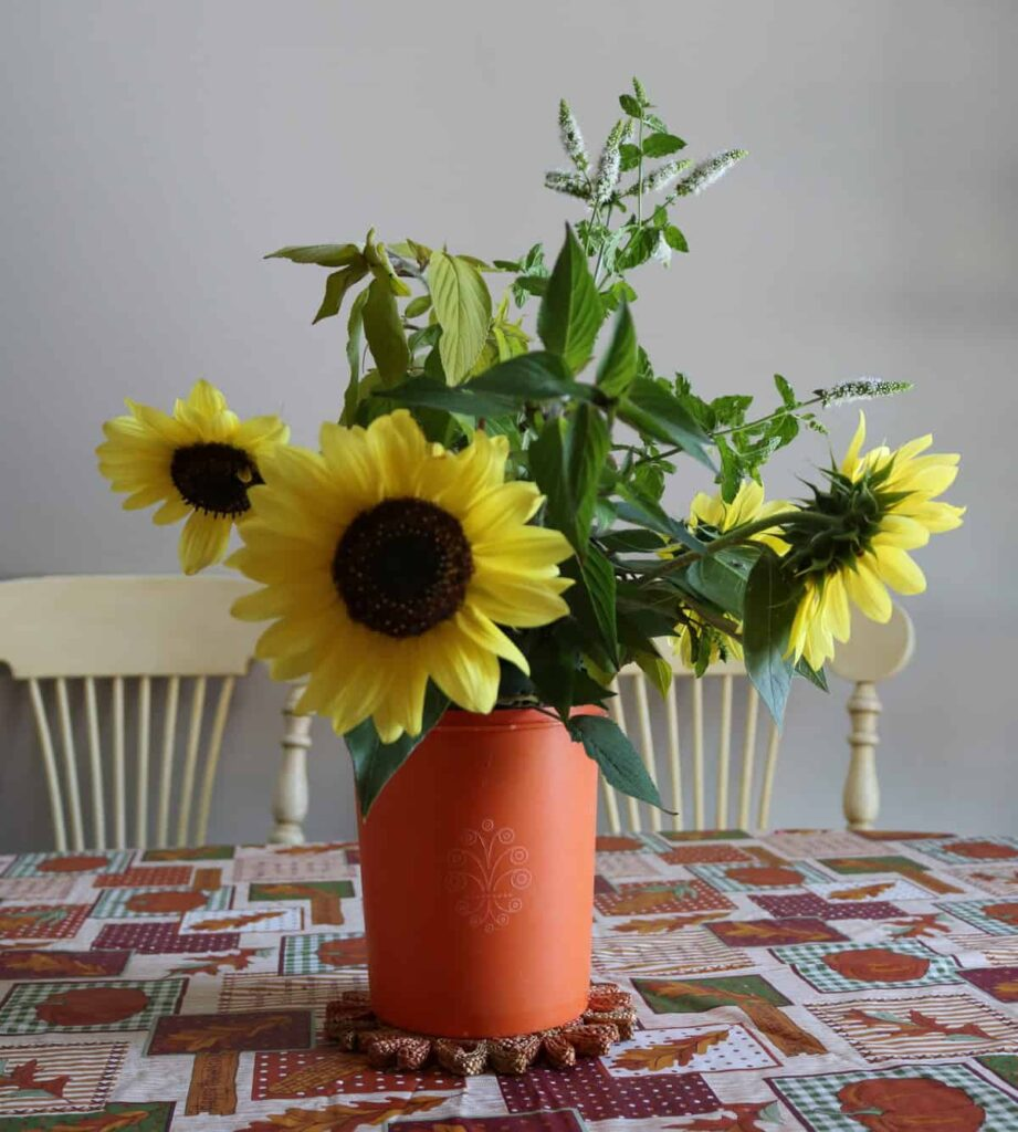 sunflowers in a vintage orange Tupperware canister