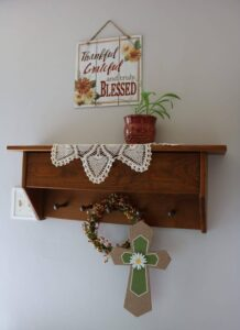 Thankful sign, plant on a wall shelf, cross on peg