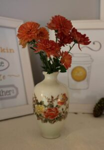 orange mums in a miniature vase