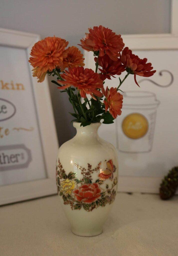 orange mums in a miniature vase