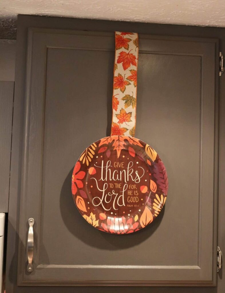 Thanksgiving paper plate and ribbon on a kitchen cupboard