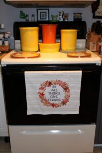 In All Things Give Thanks kitchen towel with yellow and orange vintage Tupperware canisters