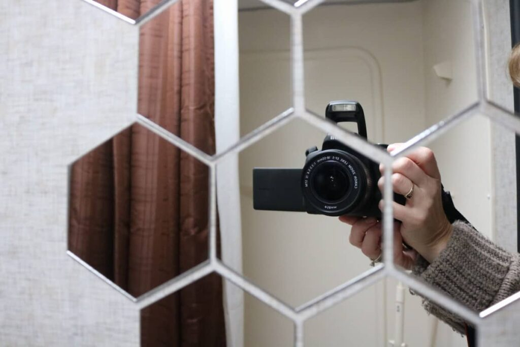 hexagon mirrors showing a camera and hand