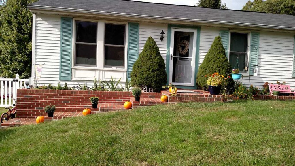 mums and pumpkins lining the brick steps in front a house