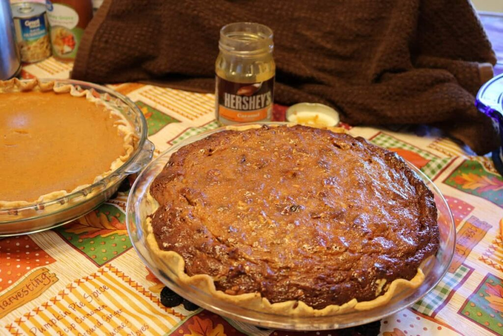 whole pie with empty caramel jar in background