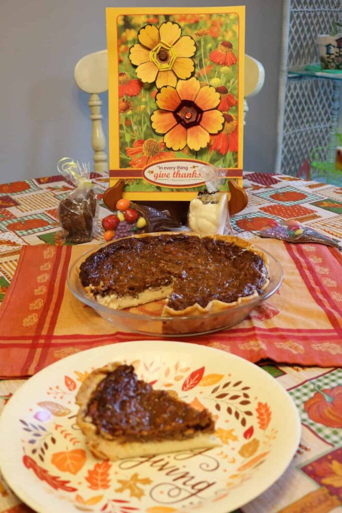 flower thanksgiving art in background, pie with piece cut out of it in middle, piece of pie on paper plate in foreground