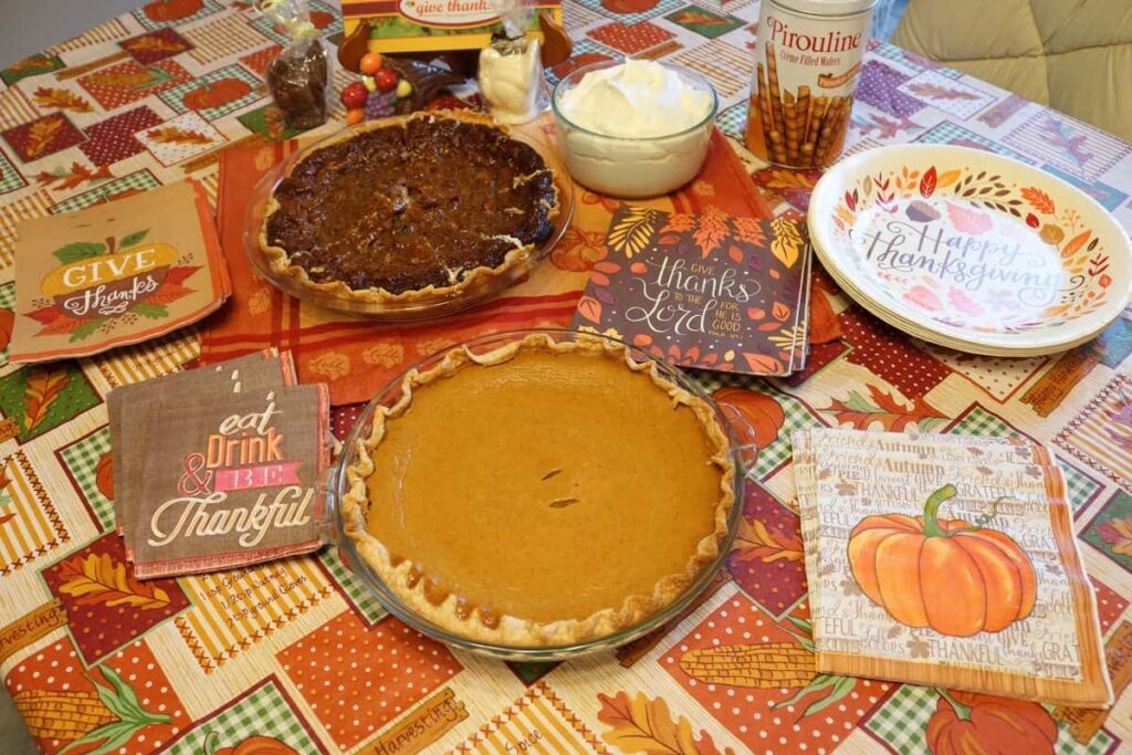 whole pumpkin pie, whole pecan pie, variety of Thanksgiving themed napkins and paper plates with bowl of whipped cream and tin of wafer rolls