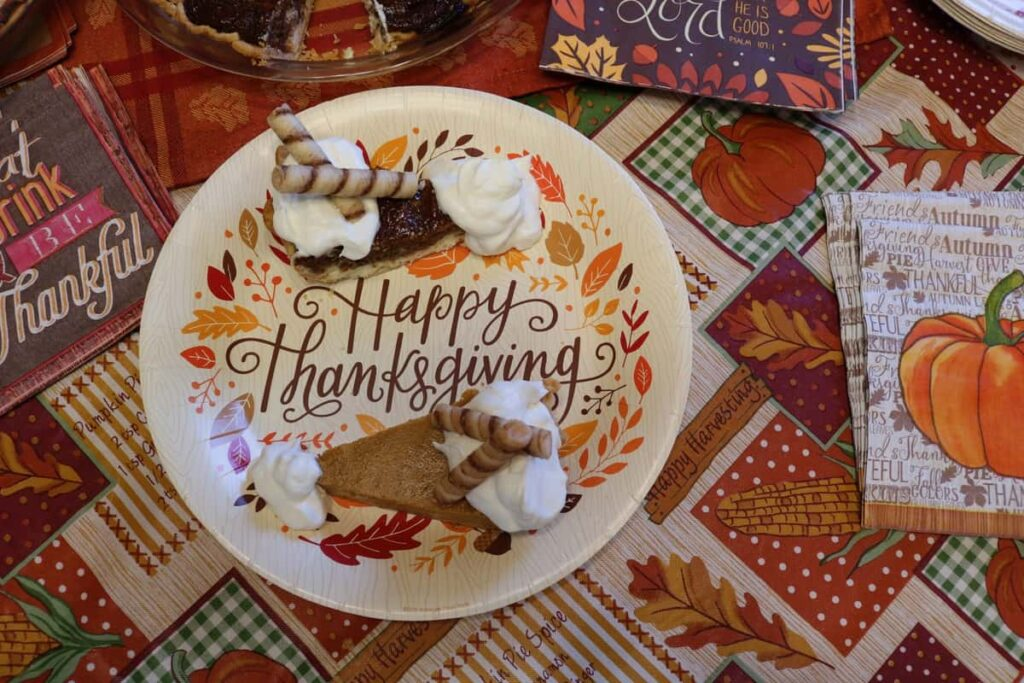 two pieces of pie on a paper plate that says Happy Thanksgiving