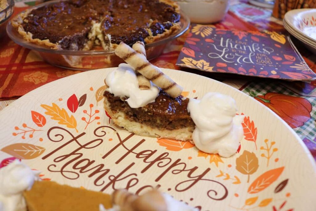 closeup of piece of pecan cheesecake pie with whip cream and wafer rolls on top, and whole pie in background