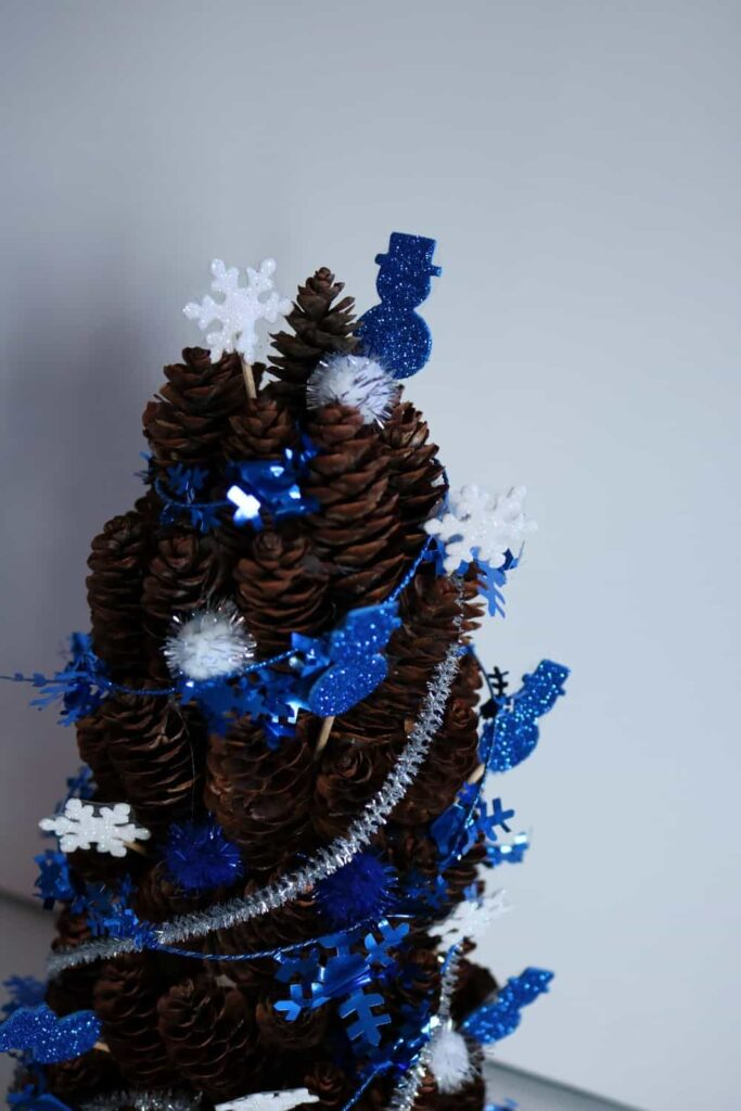 closeup of blue and white winter pine cone tree