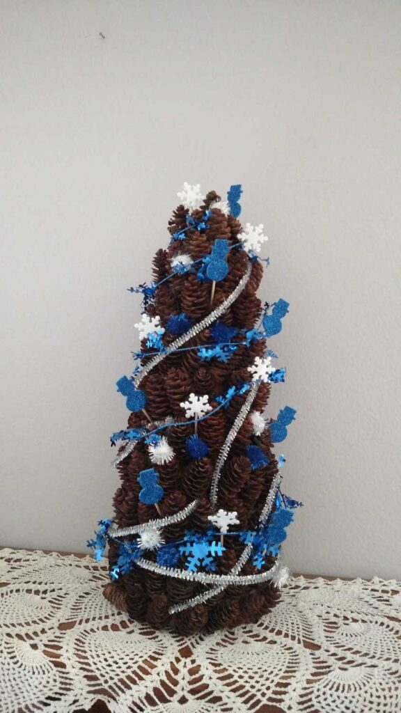 pine cone tree decorated with blue glitter snowmen, silver metallic pipe cleaners, white snowflakes, blue metallic garland, and blue pom poms