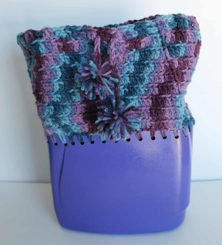 laundry detergent container with yarn crocheted onto it