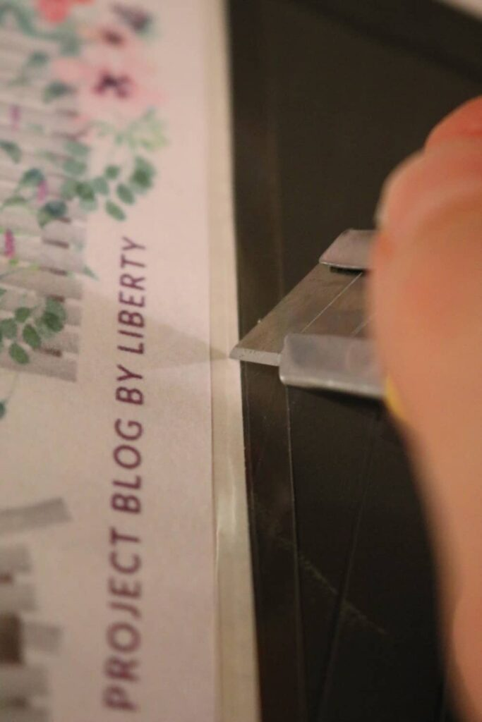 using an exacto or craft knife to cut the laminated sticker loose from its backing