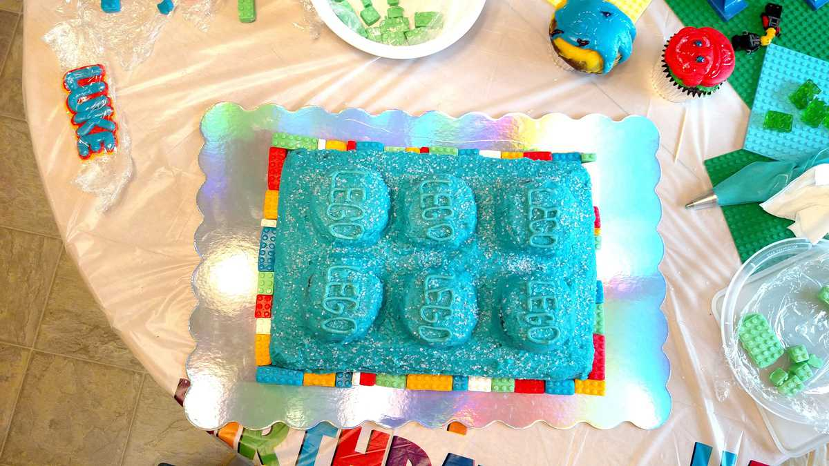 giant lego cake with blue frosting, surrounded by smaller legos bordering it