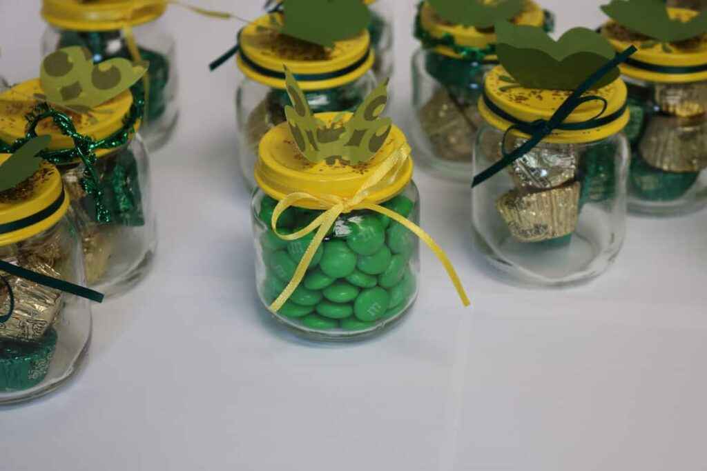 baby food jars with painted lids and candy in them