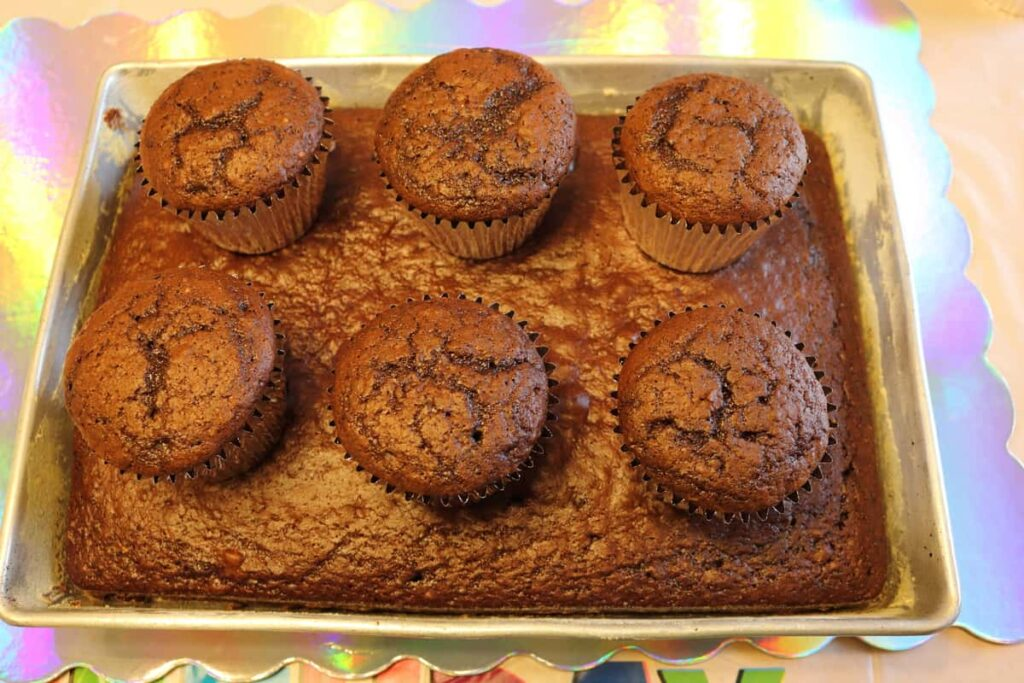 6 chocolate cupcakes on a chocolate cake