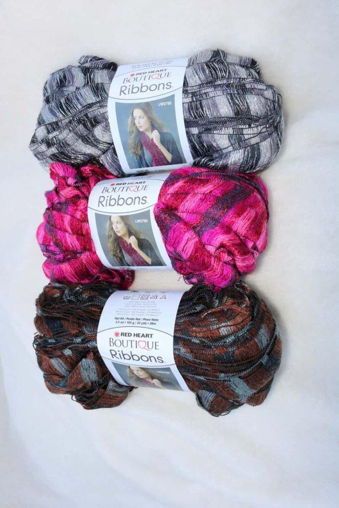 brown, pink, and black yarn, one skein of each color