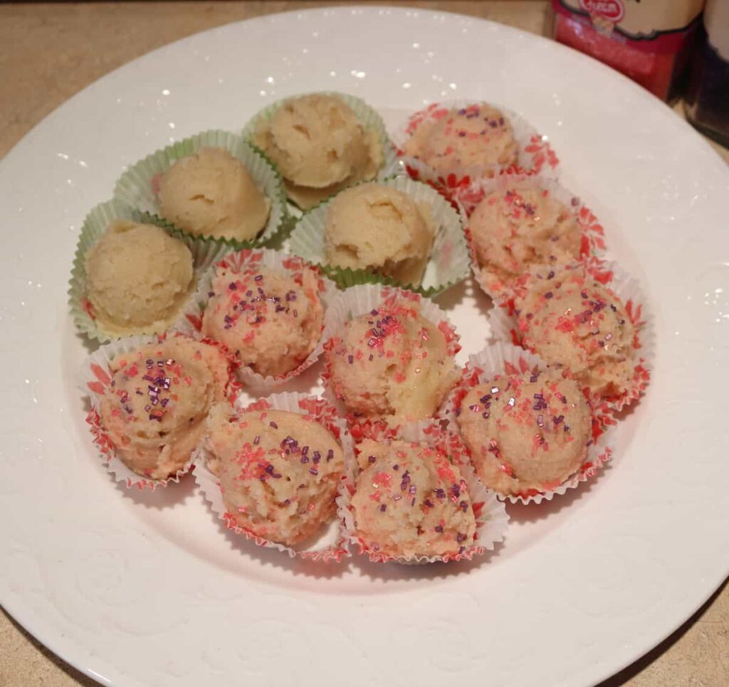 edible sugar cookie dough recipe on mini paper liners, some with sugar sprinkles and some plain