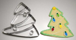 Large Christmas Tree cookie cutter next to an actual cookie made with the cutter