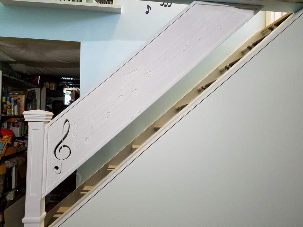 the unpainted custom stair railing https://www.b4andafters.com/music-stair-railing