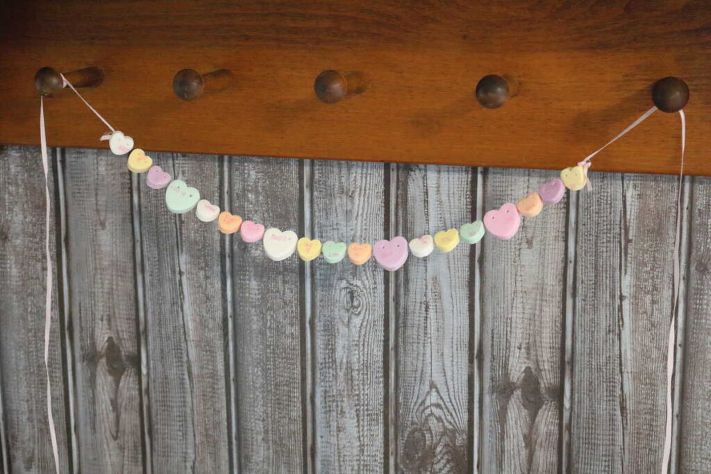 conversation heart garland tied to peg shelf for Valentine's day decor https://www.b4andafters.com/conversation-heart-necklace