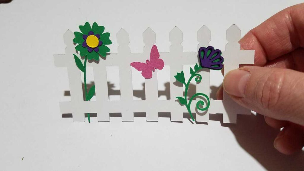 paper picket fence with paper flowers and butterfly