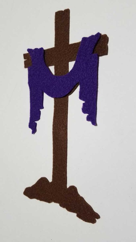 felt cross with purple cloth draped over it