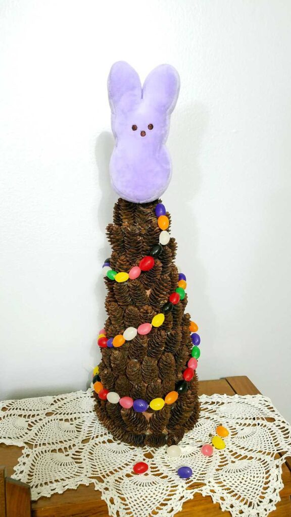 plush bunny Peep on a pine cone tree draped with a jelly bean garland